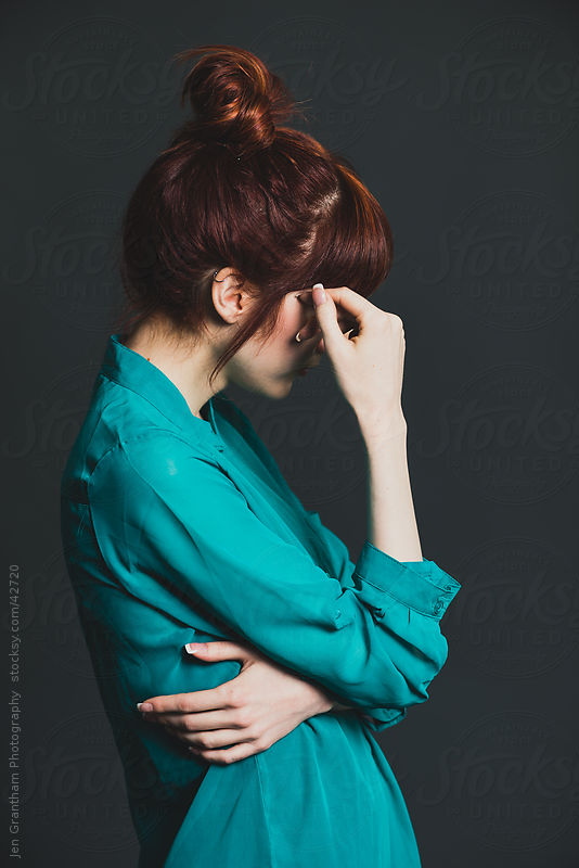 Side view of redheaded young woman covering her face