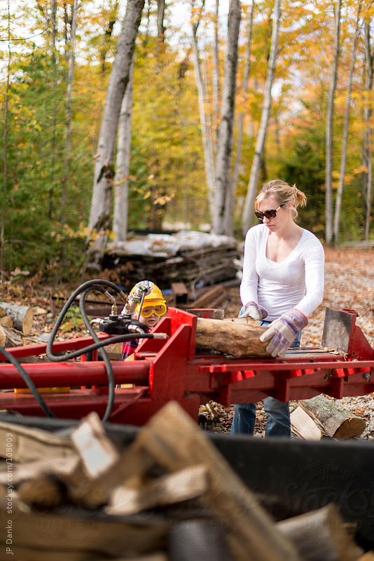 Woman and Boy Splitting Firewood for Heating In Fall at Cottage by JP Danko
