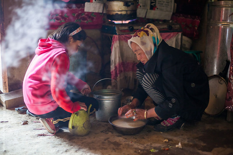Adult kyrgyz woman and daugther cooking food inside a yurt, China by Matteo Colombo
