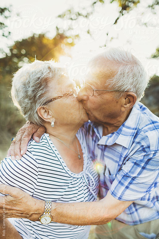 Elderly couple kissing in the sunshine by Rob Campbell