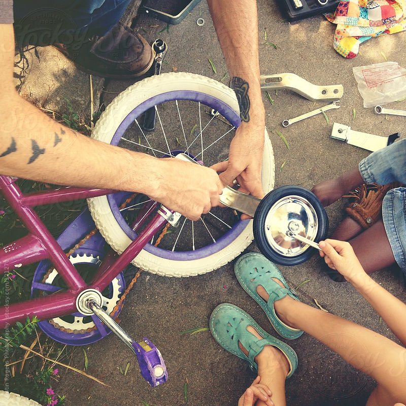 father putting training wheels on bike with children by Kristin Rogers Photography