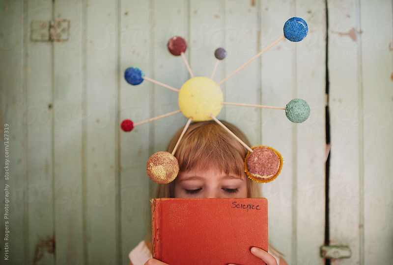 Young girl with playing with her homemade solar system craft by Kristin Rogers Photography