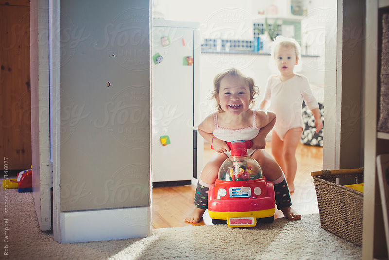 Toddler girl riding toy car having fun by Rob Campbell