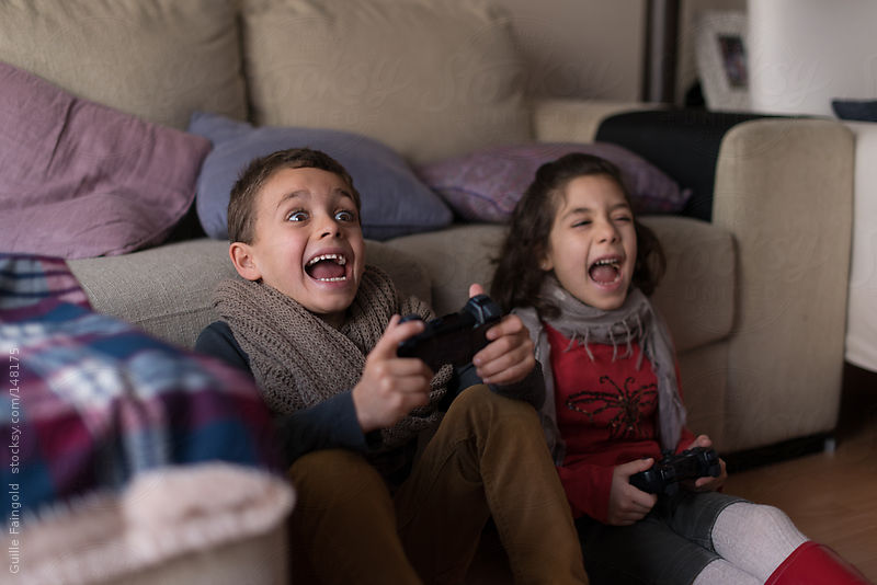 Children enjoying game console at home by Guille Faingold