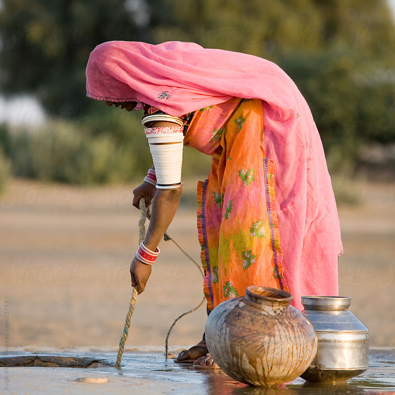 Indian woman wearing sari pulling water from well in desert. by Hugh Sitton