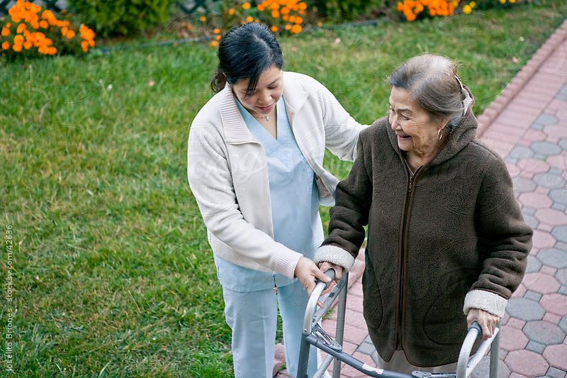 Homecare Provider Helps Elderly Patient Exercise with Walker by Joselito Briones