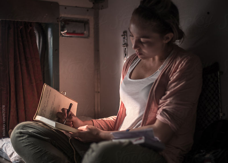A young woman traveller updating her daily journal while on a train by Mike Marlowe