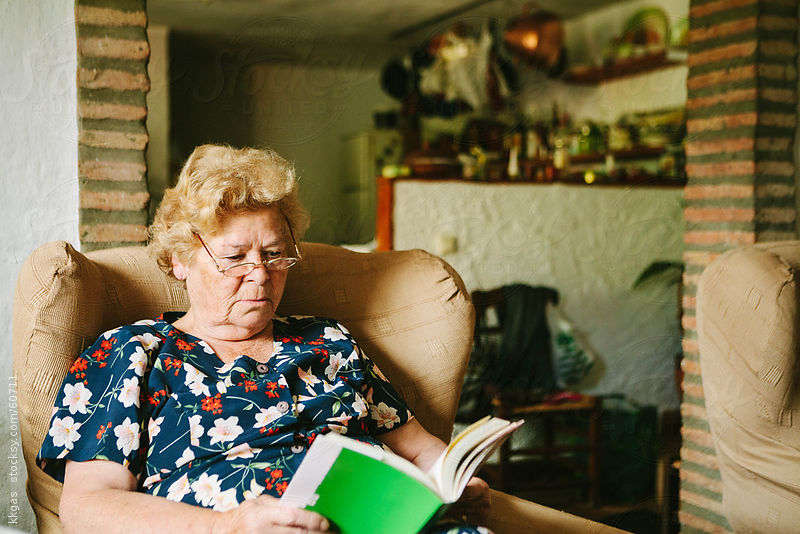 Senior woman reading in her living room. by kkgas
