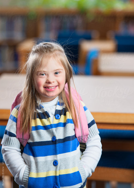Smiling Girl Student with Down Syndrome in School Library by Brian McEntire