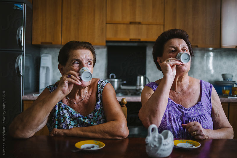Two seniors women drinking coffee by Simone Becchett