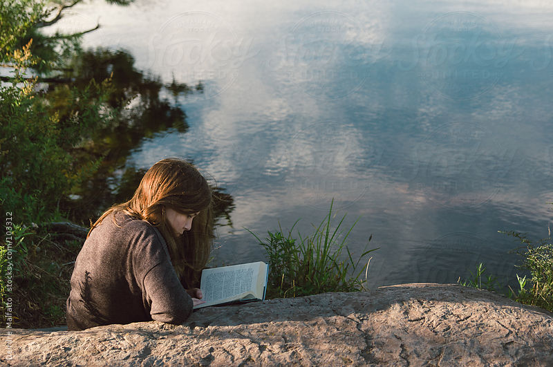 girl reading book on rock by lake by Deirdre Malfatto