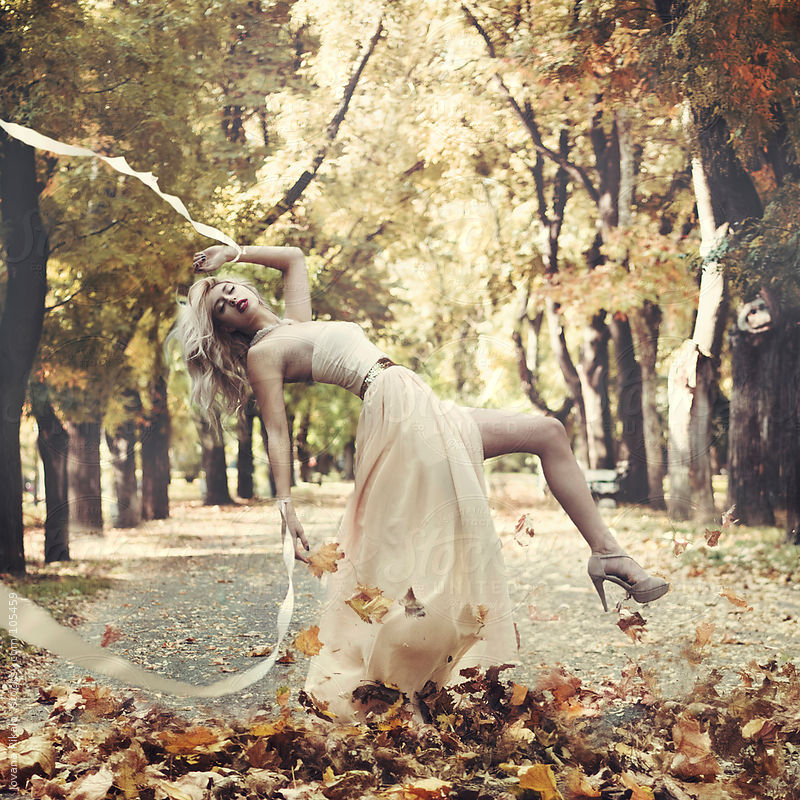 A beautiful young woman surrounded by leaves with silk tapes on her hands by Jovana Rikalo