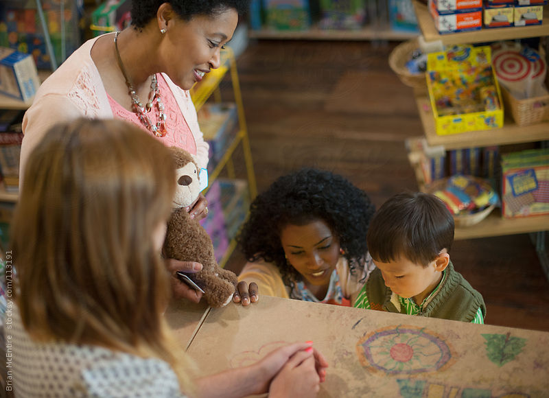 Little Boy Checks Out Toys At Counter In Store with Mother and Grand Mother by Brian McEntire
