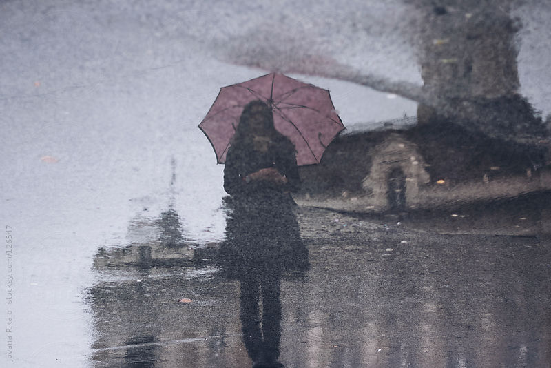 Silhouette puddle reflection of girl standing and holding umbrella by Jovana Rikalo