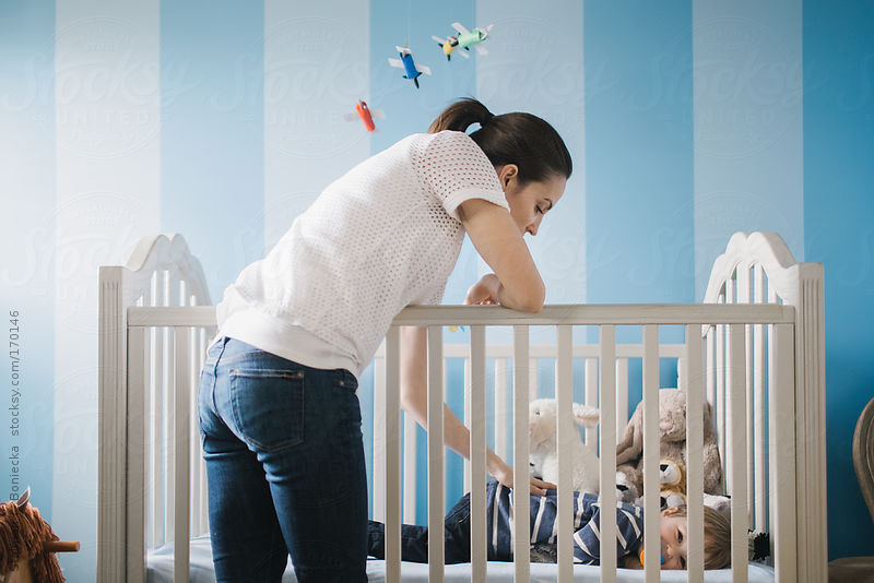 Mom putting son to bed in his crib by Stalman & Boniecka
