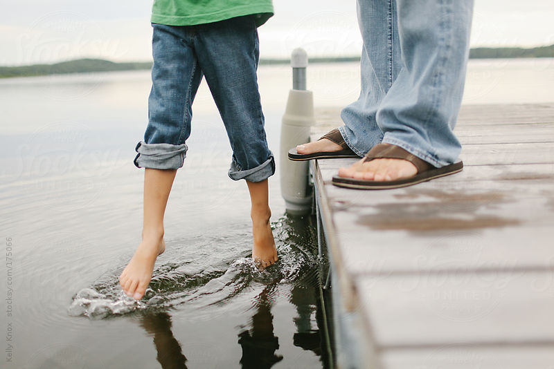 father dangles his son over water by Kelly Knox