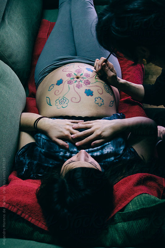 Pregnant belly mandala painting by an artist on young woman belly from above by Alejandro Moreno de Carlos