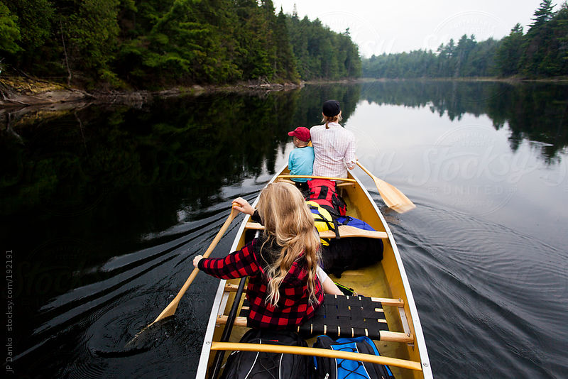 Family Relaxing On Quiet Lake Wilderness Camping Trip in Canoe by JP Danko