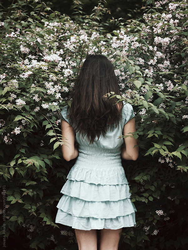 Back view of a young woman standing in front of a bush by Jovana Rikalo