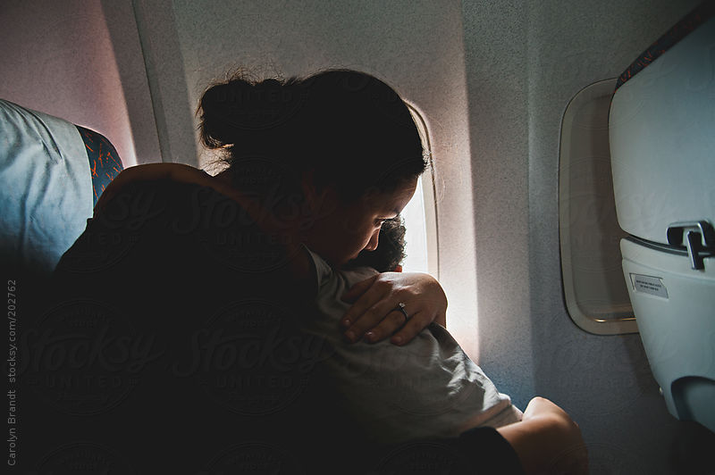 Mother holds son on airplane by Carolyn Brandt