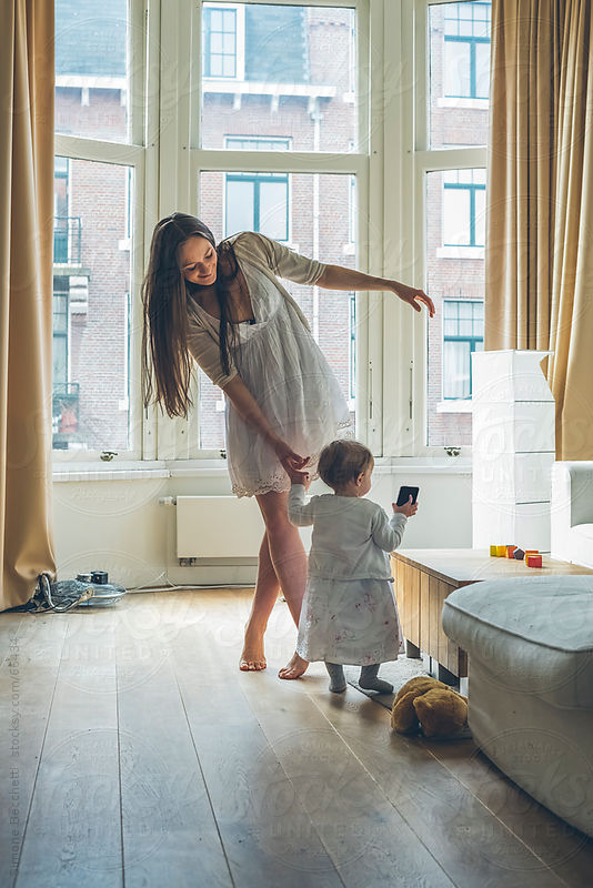 Mother playing with her little girl at home by Simone Becchetti