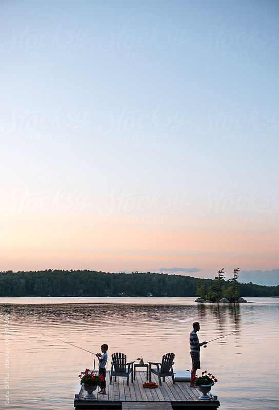 Father and son fish together on a lake at dusk by Cara Slifka