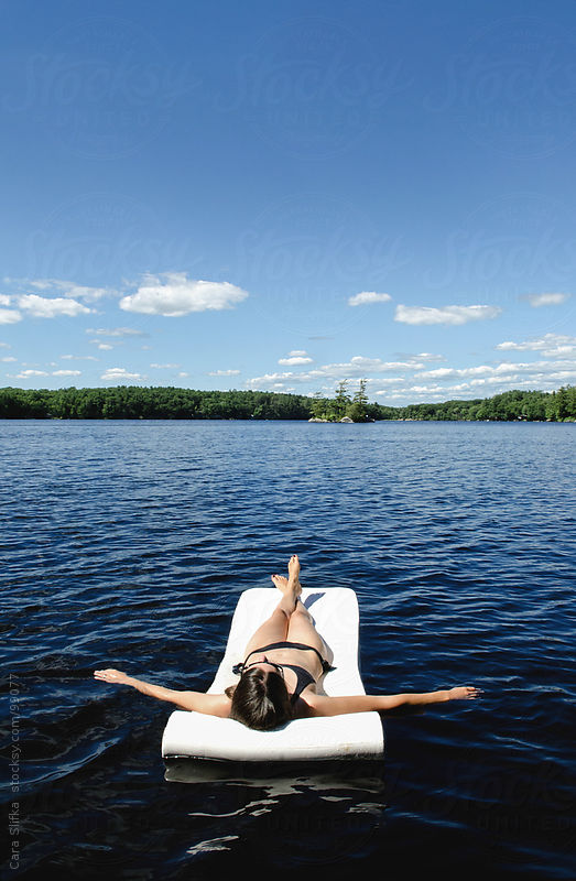 Woman in black bikini floats on a lake in summer by Cara Slifka
