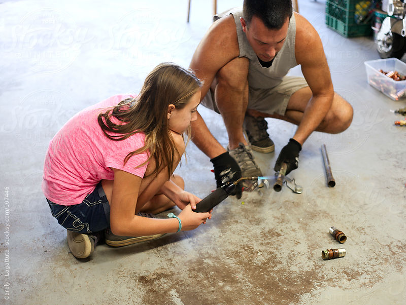Father and daughter soldering a copper pipe by Carolyn Lagattuta