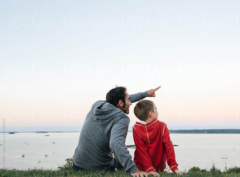 Father and son sit together enjoying the sunset and pointing at something in the distance by Cara Slifka