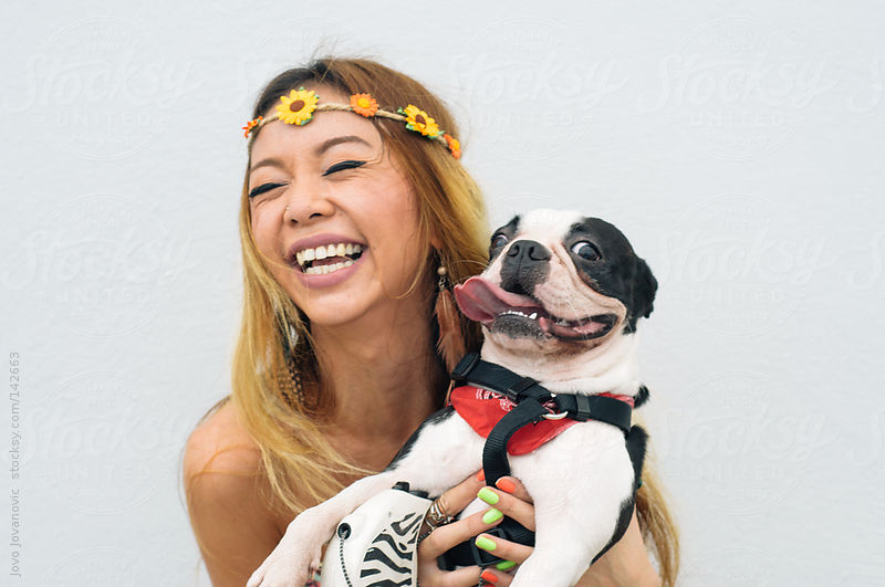 Blond Asian woman holding her happy, smiling dog. by Jovo Jovanovic