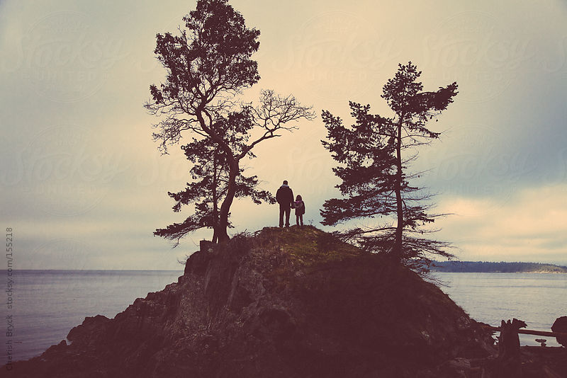 Father and daughter on a hill top at the shore. by Cherish Bryck