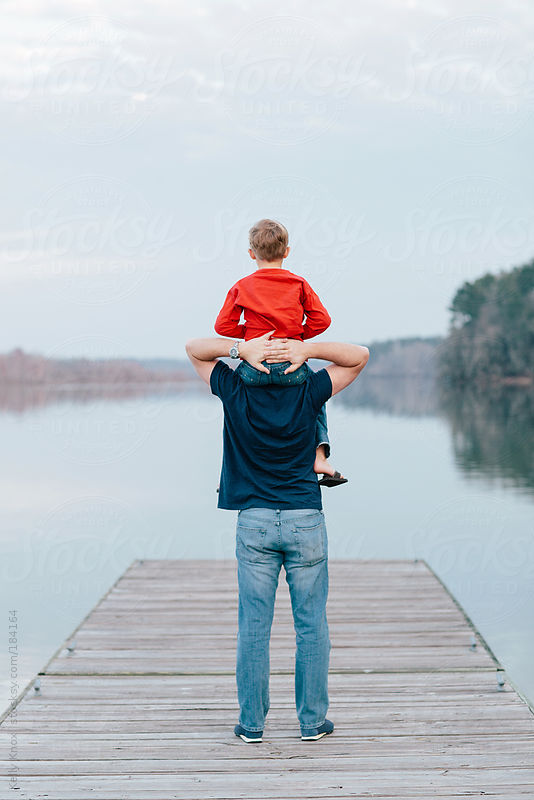 father and son standing on a pier by Kelly Knox