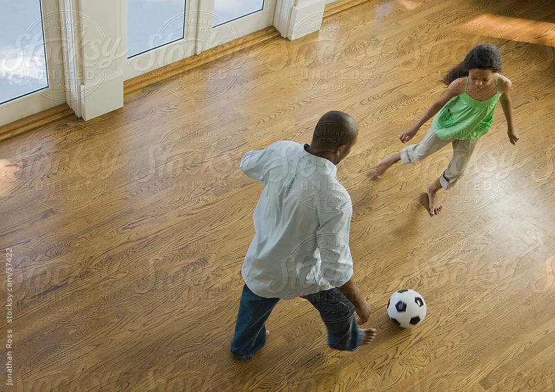 Man with daughter (12-13) playing soccer at home by Andersen Ross Photography