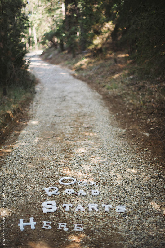 "The Words ""Our Path Starts Here"" on a Gravel Road by Briana Morrison"