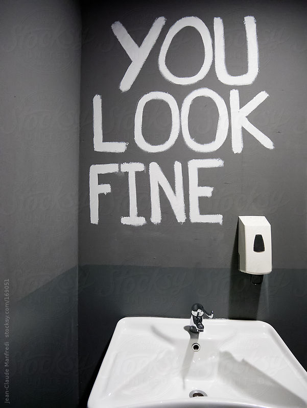 Sign on a wall saying: you look fine. Toilet where you do not need the mirror by Jean-Claude Manfredi