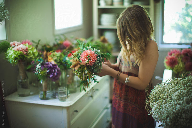 Girl in dress putting together a bouquet of flowers by Kevin Gilgan