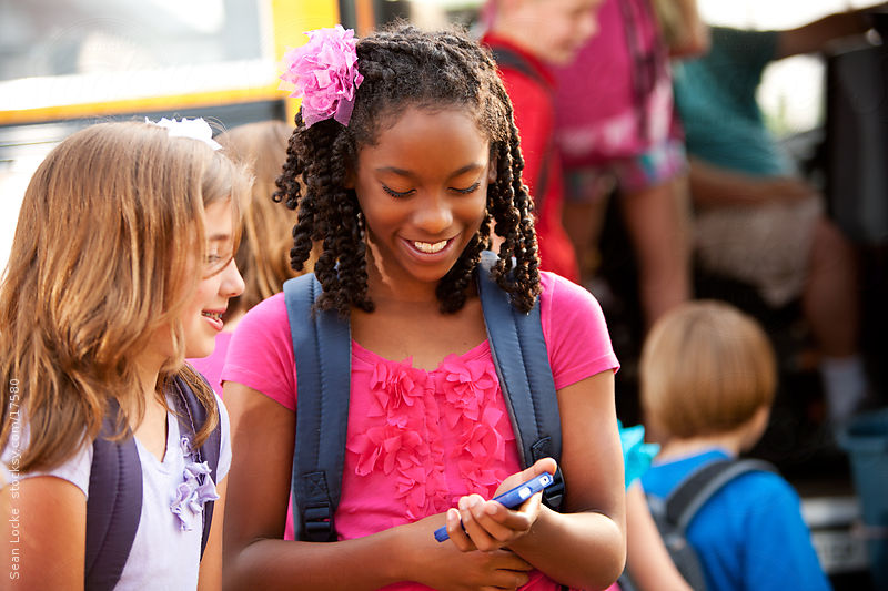School Bus: Kids Use Cell Phone in Line by Sean Locke