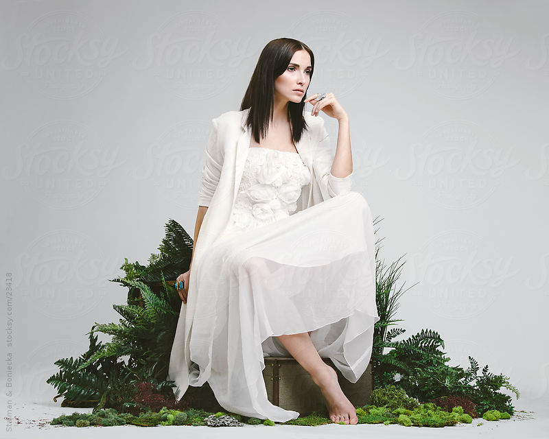 A beautiful brunette sitting in a studio in a wedding dress by Stalman & Boniecka