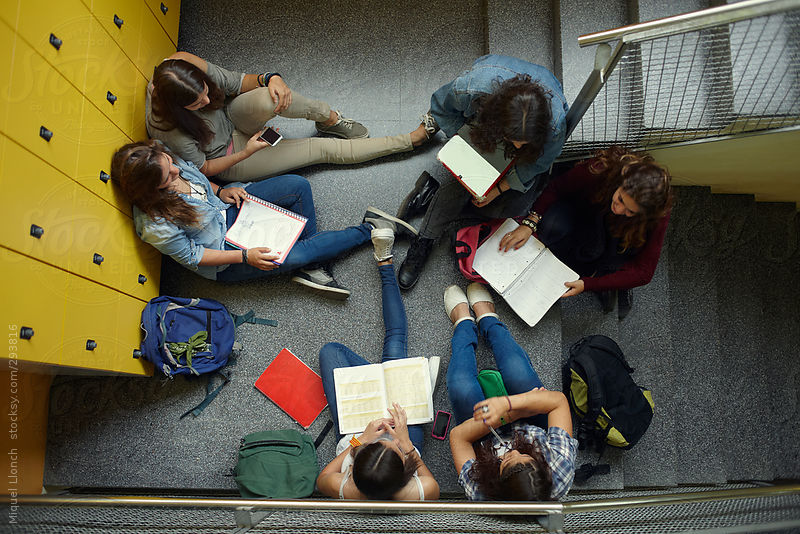 Group of students sitting at the stairs of the school by Miquel Llonch