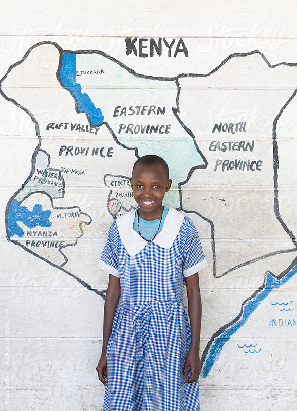 School girl standing in front of map of Kenya. by Hugh Sitton