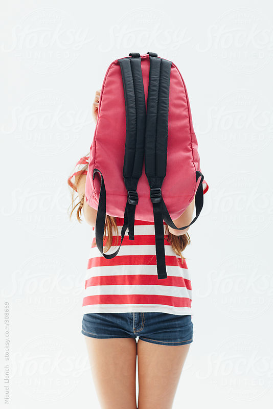 Girl hiding behind her school backpack by Miquel Llonch