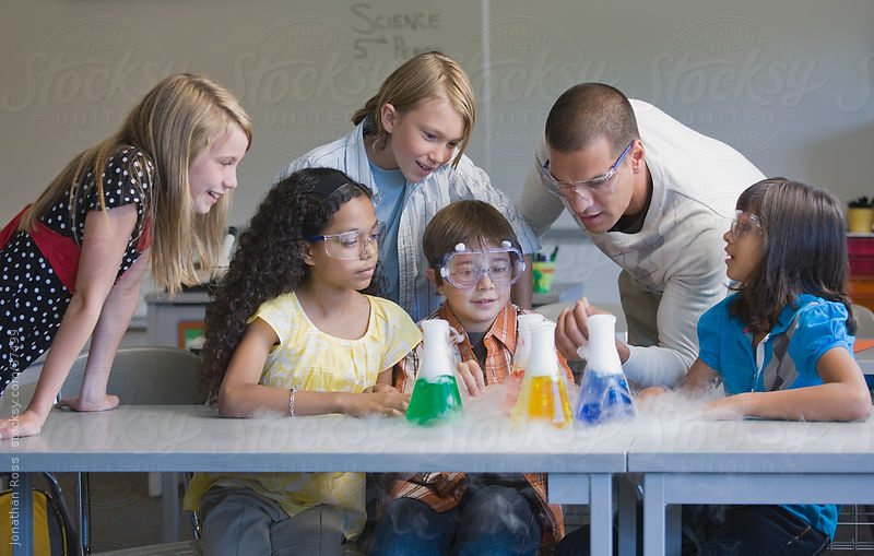 Children (10-11) and teacher at science class by Andersen Ross Photography