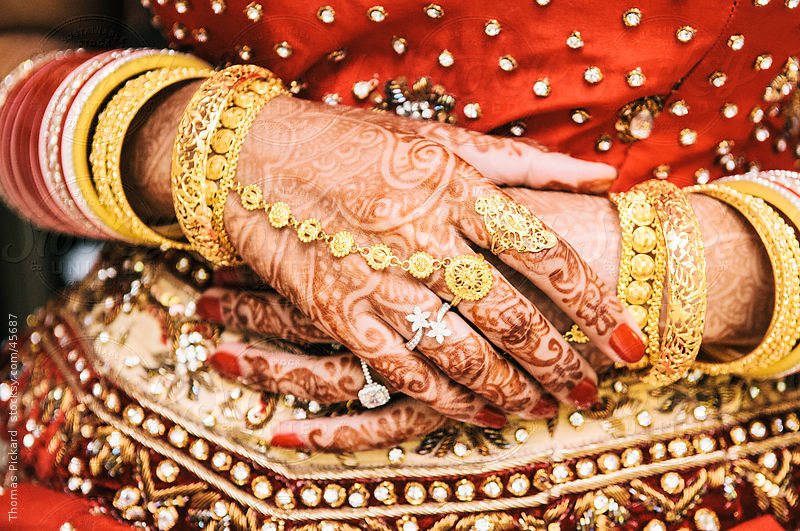 Indian woman's hands painted with henna, prior to a wedding ceremony. by Thomas Pickard
