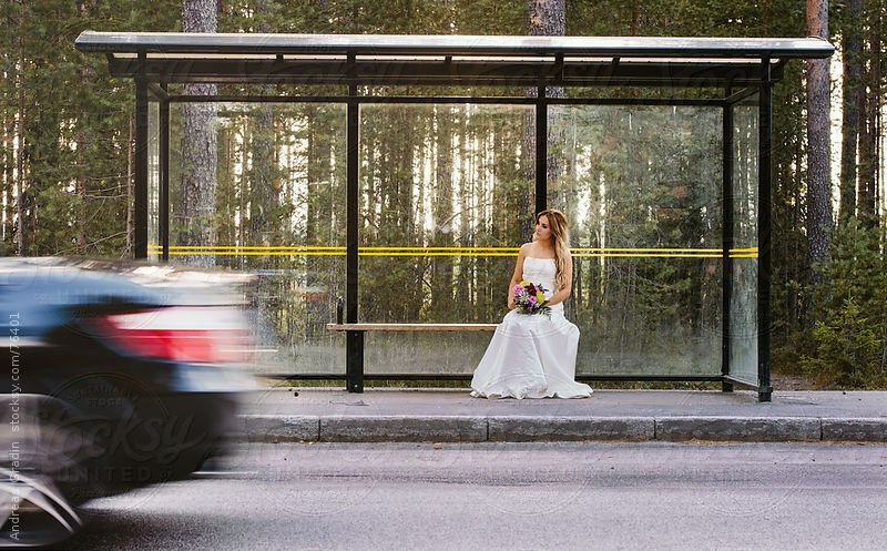 a lonely bride waiting on a bus stop by Andreas Gradin