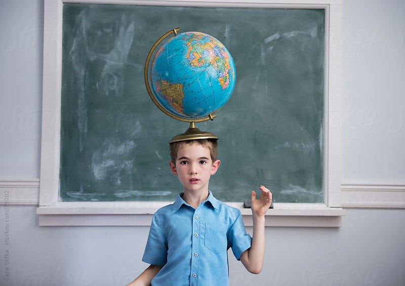 Boy in a classroom balances a globe on his head by Cara Slifka