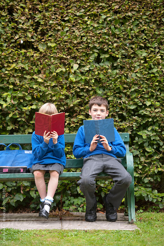 two children in school uniform reading books on a park bench by Lee Avison