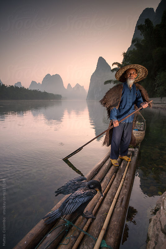 Fisherman on bamboo raft on the Li river, near Guilin, China by Matteo Colombo