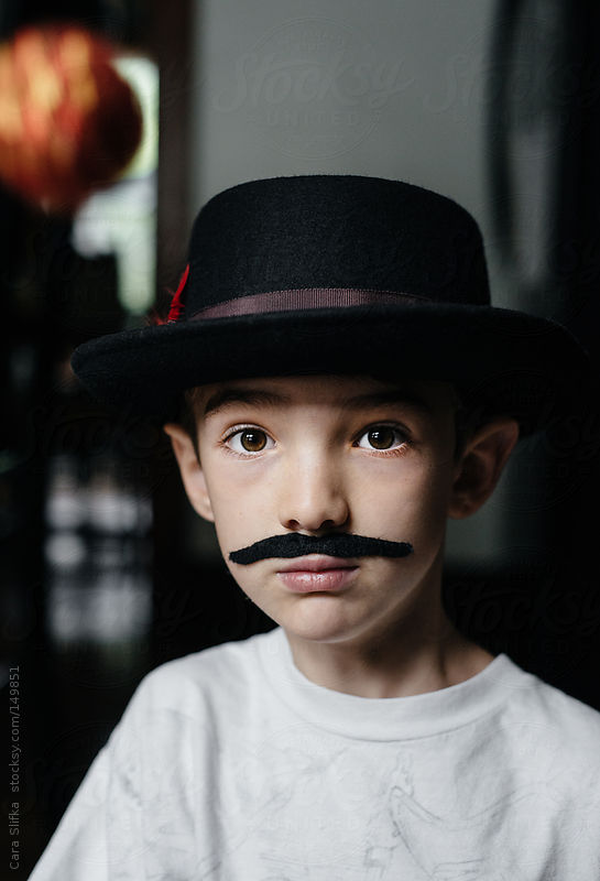 Portrait of a boy wearing a vintage hat and fake mustache by Cara Slifka