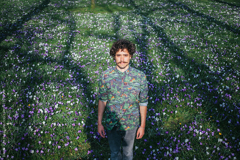 Young stylish man standing in a grass field with flowers enjoying the first days of spring by Denni Van Huis