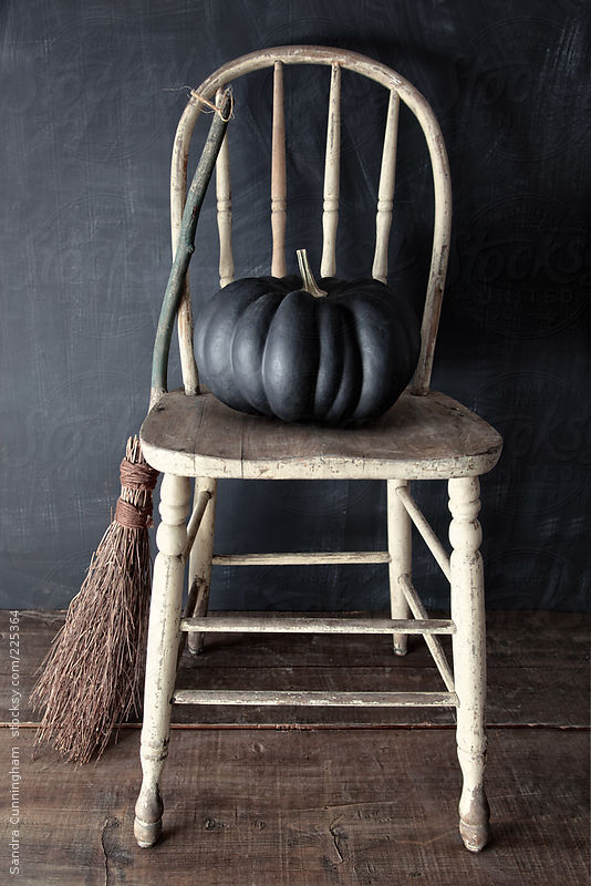 Black pumpkin on chair by Sandra Cunningham